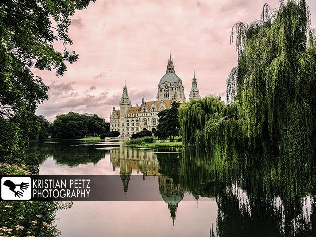 Deutschland, Hannover, Blick auf das Neue Rathaus und seine Spiegelung auf dem Maschteich bei farbenfrohen Sonnenaufgang.