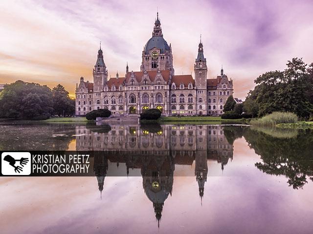 Deutschland, Hannover, Blick auf das Neue Rathaus und seine Spiegelung auf dem Maschteich während farbenfrohen Sonnenuntergang.
