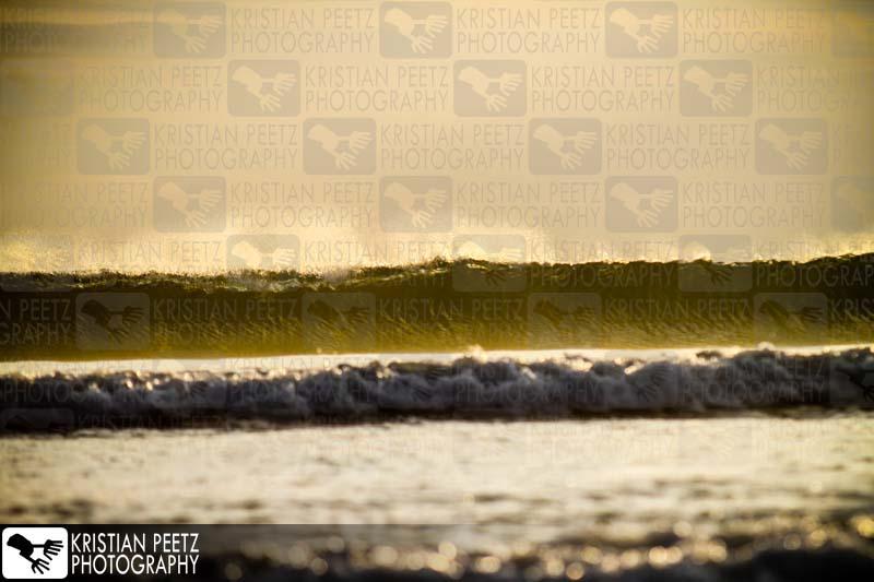 Indonesien, Bali, Wellen brechen bei Sonnenuntergang am Strand von Kuta.